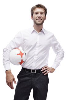 Young man holding soccer ball, smiling, portrait - BMF00542