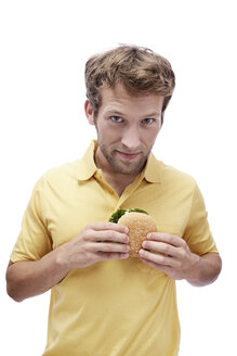 Young man holding Hamburger, portrait - BMF00533