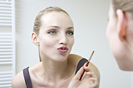 Young woman holding lip brush, puckering lips - WESTF10817