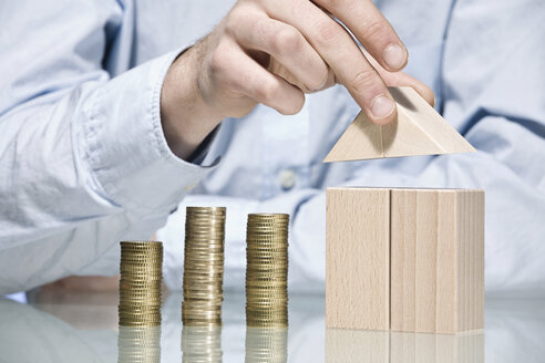 Person building house with building bricks beside stack of coins, close up - CLF00695