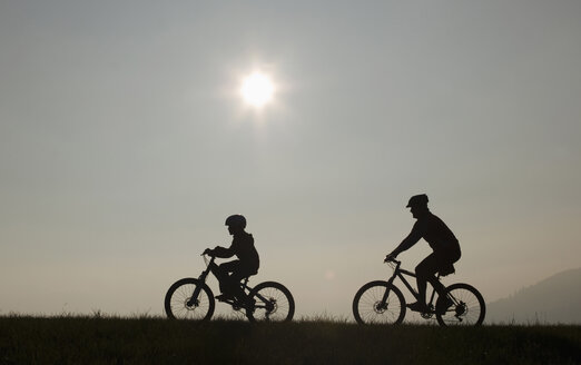 Father and son (10-11) riding mountain bikes, silhouette - WWF00845