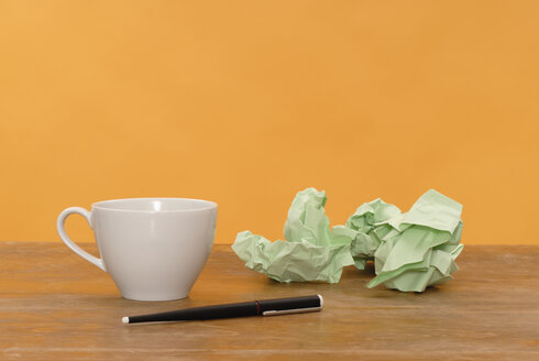Cup of coffee, pen, paper balls, close up - KJF00037