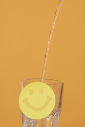 Water being poured into glass, Smiley in foreground - KJF00031