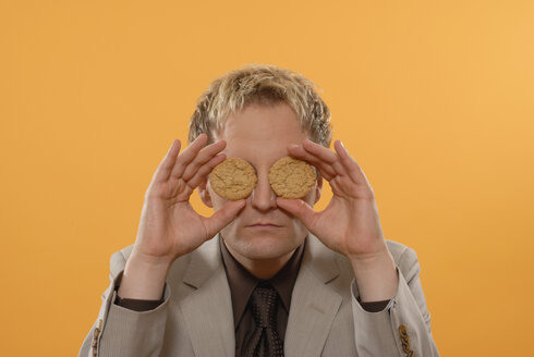Businessman covering eyes with cookies, portrait - KJF00022