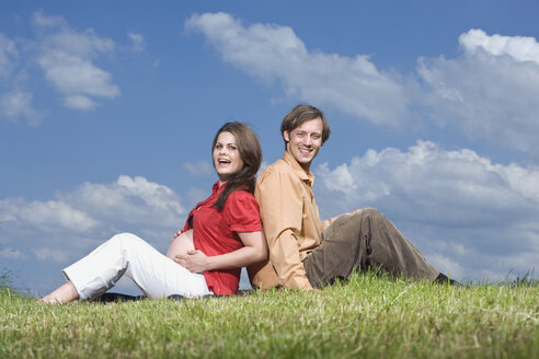 Couple sitting back to back in meadow, smiling, portrait - RDF00957