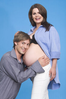 Man hugging his pregnant wife's belly, portrait - RDF00954