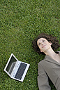 Young Business woman lying on a lawn with a laptop beside her, elevated view, portrait - KJF00063