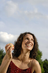 Young woman holding apple, smiling, portrait - KJF00060