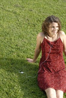 Young woman sitting on lawn, listening to MP3 player, smiling - KJF00057