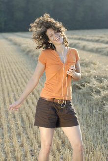 Young woman in field, dancing, listening to MP3 player - KJF00054
