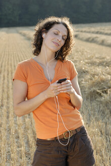 Young woman in field listening to MP3 player, portrait - KJF00051