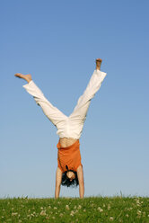 Young woman doing handstand on meadow - KJF00042