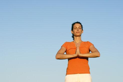 Woman exercising yoga, eyes closed, portrait - KJF00039
