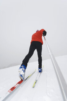 Italy, South Tyrol, Man cross-country skiing, rear view - WESTF11288