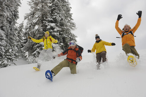 Italy, South Tyrol, People with snowshoes fooling about - WESTF11230