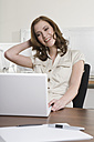 Germany, Munich, young woman in office, using laptop, smiling, portrait - LDF00653