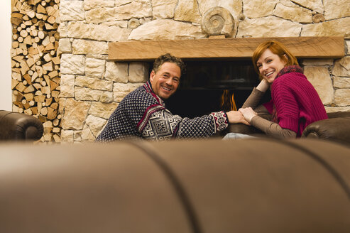 Couple sitting by fireside, smiling - WEST11544