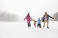Italy, South Tyrol, Seiseralm, Family holding hands, ice skating - WEST11733