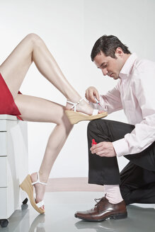 Germany, Business people in office, Man painting woman's toenails - MAEF01653