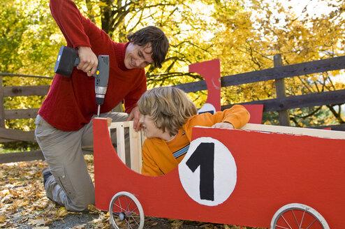 Austria, Salzburger Land, Young man fixing soapbox car, boy (12-13)  watching - HHF02927