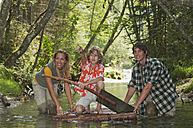 Austria, Salzburger Land, Boy kneeling on timber raft, Parents wading in creek - HHF02909