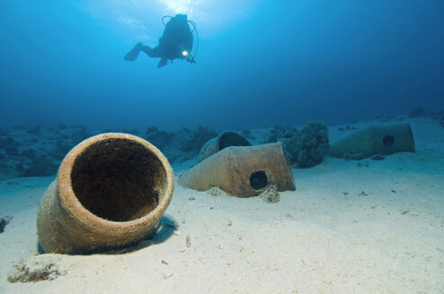 Egypt, Red Sea, Scuba diver and amphoras on ocean bed - GNF01157