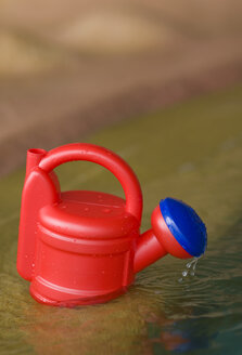 Germany, Baden-Württemberg, Plastic watering can standing on pool edge - SMF00454