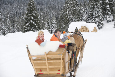 Italy, South Tyrol, Seiseralm, Family sitting in sleigh, smiling, portrait - WESTF11472