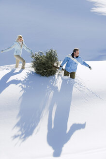 Italy, South Tyrol, Seiseralm, Couple carrying Christmas tree in snow - WESTF11445