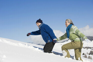 Italy, South Tyrol, Seiseralm, Senior couple walking in snow, side view, portrait - WESTF11415