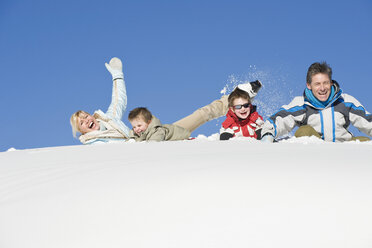 Italy, South Tyrol, Seiseralm, Family lying in snow, laughing, portrait - WESTF11412