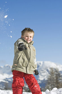 Italy, South Tyrol, Seiseralm, Boy (3-4) throwing snow in the air, portrait - WESTF11406