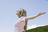Germany, Bavaria, Munich, Young woman, arms outstretched, smiling, portrait - CLF00725
