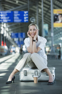 Germany, Leipzig-Halle, Young woman in Airport departure lounge, sitting on suitcase - WESTF12065