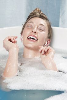 Young woman in bathtub listening to music - WESTF12000