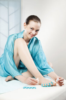 Germany, Bavaria, Munich, Young  woman painting her toenails - WESTF11967