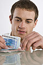 Young man counting Euro notes, portrait - RBF00092
