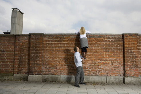Germany, Bavaria, Munich, Young man helping young woman to climb a wall - RBF00089
