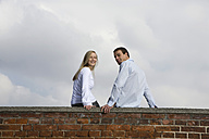 Germany, Bavaria, Munich, Young couple sitting on top of brick wall - RBF00083
