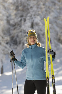 Austria,Tyrol, Seefeld, Wildmoosalm, Woman holding cross-country skis - MIRF00007