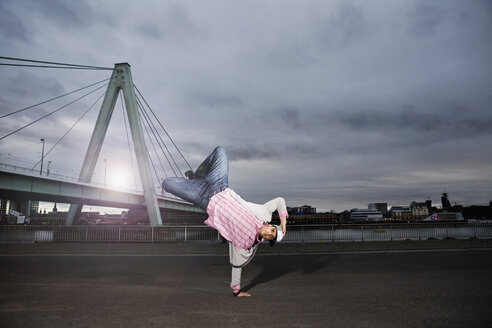 Germany, Cologne, Young man performing breakdance, Rhine bridge in background - SK00010