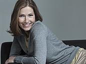 Woman on sofa, smiling, portrait - WEST12274
