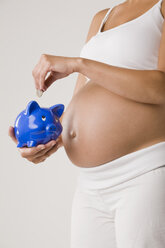 Pregnant woman putting Euro coin in piggy bank, mid section - LDF00700