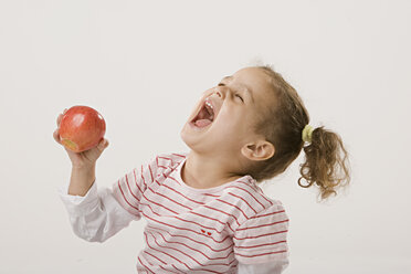 Girl (2-3) holding an apple, laughing, side view, portrait - LDF00694