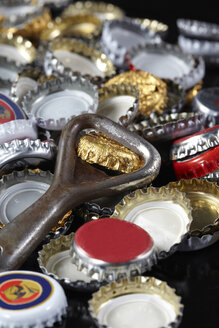 Bottle opener and crown caps, close-up - TLF00347