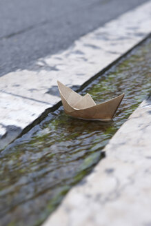 France, Paper Boat floating in gutter - THF01070