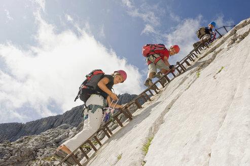 Germany, Garmisch-Partenkirchen, Alpspitz, Mother and sons (10-11), (12-13) climbing rock face on ladder - RNF00005