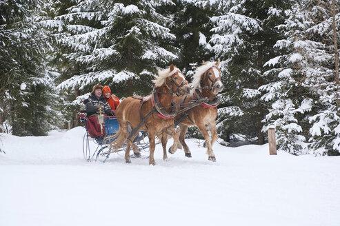 Austria, Salzburger Land, Couple riding in sleigh - HHF03025
