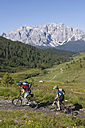 Italy, Dolomites, Couple mountainbiking, elevated view - FFF01084