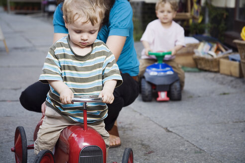 Germany, Berlin, Mother and boy (2-3) (3-4) on toy tractor, close-up - WESTF13593
